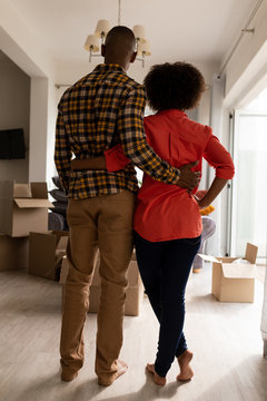 Couple standing together with arm around in living room at home