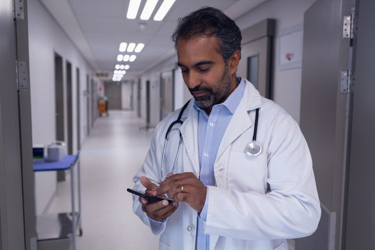 Mature male doctor using mobile phone in hospital corridor