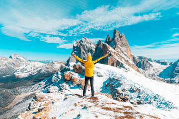 Man celebrating success at top of snowy mountain