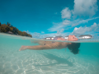 Woman swim and relax in the sea at Maldives islands