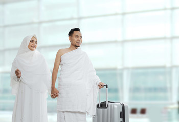 muslim couples wife and husband wearing white traditional clothes for Ihram ready for Hajj walk in the airport