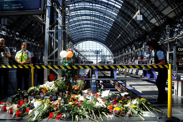 Messages of mourning, candles and flowers are placed by people for an eight-year-old boy who was pushed by a man in front of an oncoming train and died at the main train station in Frankfurt