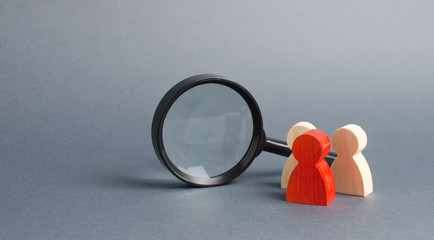 Fototapeta Three wooden human figure stands near a magnifying glass on a gray background. The concept of the search for people and workers. Search for vacancies and work. Human resources, management. obraz