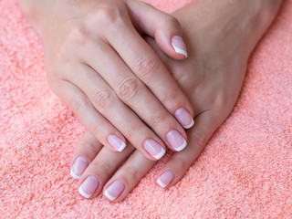 Closeup french manicure in a beauty salon. Woman hand care. Beauty woman nails