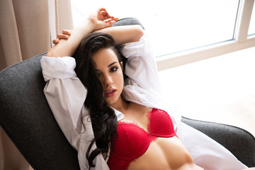sexy young girl in red underwear and white shirt sitting on armchair and looking at camera