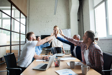 Happy successful multiracial business team giving a high fives gesture as they laugh and cheer their success.