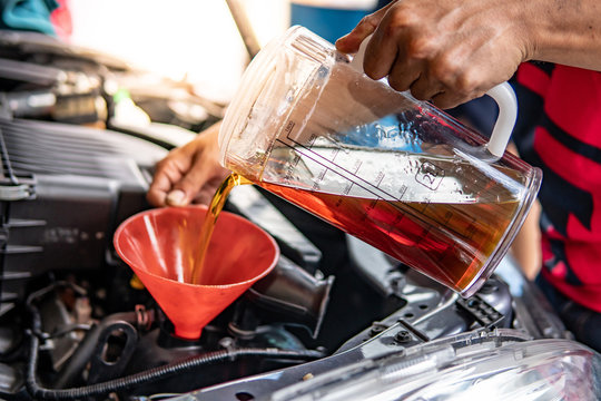 Auto mechanic hand pouring and replacing fresh oil into car engine at auto repair garage. Automobile maintenance and industry concept