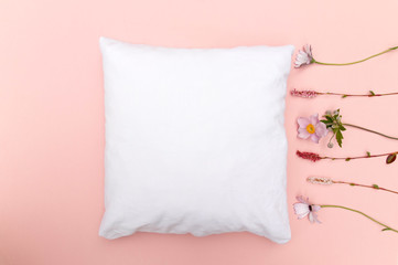 Blank white cushion mock up on pink background with wild flowers right and space left - empty and ready to add your own design