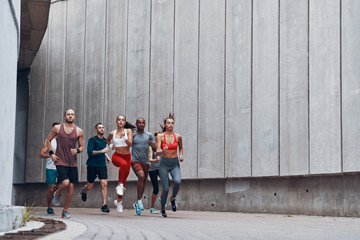 Full length of young people in sports clothing jogging while exercising outdoors Wall mural