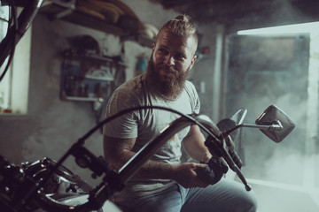 Handsome bearded man sits on a motorcycle seat and looks away