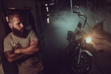 Handsome brutal man with a beard is standing in his garage against the background of a motorcycle...