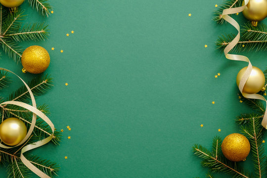 Christmas frame made of fir branches, gold decorations, Christmas balls, confetti on green background. Christmas background. Xmas or New year banner mockup template. Flat lay. top view, copy space
