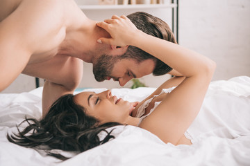 side view of handsome man kissing woman lying on bed