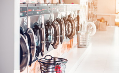 Row of industrial laundry machines in laundromat  in a public laundromat, with laundry in a basket , .Thailand