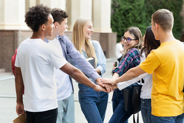 Togetherness, unity concept. Students putting their hands together