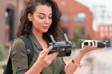 Young beautiful woman launching drone quadcopter at urban background.