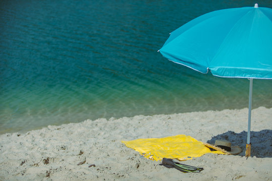view of sun blue umbrella with yellow blanket on sand beach