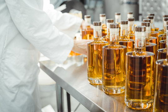 Small liquor production based on maple syrup. Lot of pure alcohol bottles unlabeled. Bottles placed in a row. Person in lab coat analyzing the bottles.