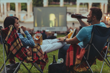 couple sitting in camp-chairs in city park looking movie outdoors at open air cinema Fotomurales