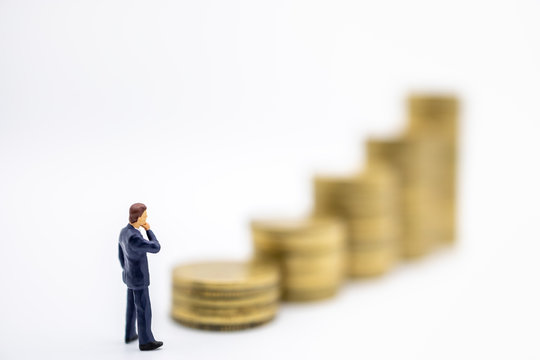 Succession, Finance, Business, Money, Security and Saving Concept. Close up of businessman miniature figures standing and looking tp stack of gold coins on white background and copy space.