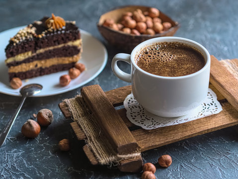 Breakfast. Coffee morning , with a slice of cake and hazelnuts on a textural background.