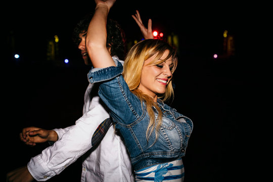 Happy young woman dancing back to back with a man at summer night festival