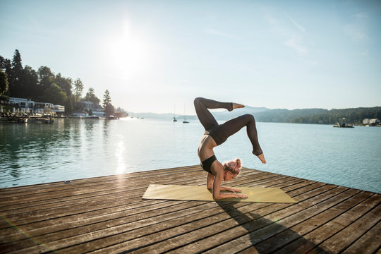 Woman practicing yoga on jetty at lake
