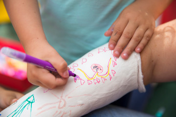 Little girls painting her mother's plaster arm