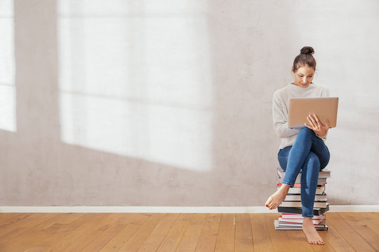 Young woman sitting on stack of books using laptop at home