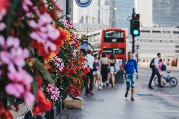 Photo on textile frame London red bus Unidentified people walking on a street in London, UK, blossoming flowers.