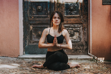 Woman practices yoga and meditates in the gomughasana position