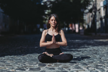 Woman practices yoga and meditates in the lotus position