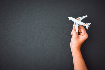 man's hand holding white toy airplane model over black color wall background with copy space, concept of travel Fototapete