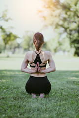 Beautiful young woman practicing yoga and stretching in city park