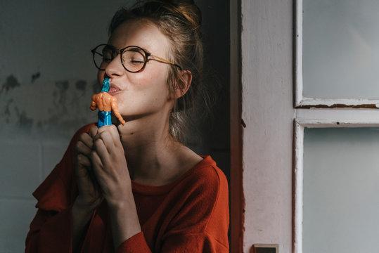 Young woman kissing superhero comic figurine