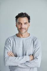 Portrait of smiling man with stubble wearing grey sweatshirt