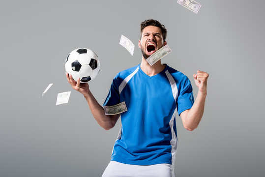 soccer player with ball cheering with clenched hand near falling money on grey