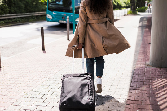Young woman with luggage at bus stop