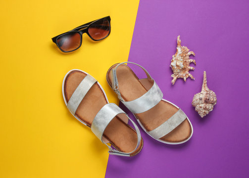 Creative summer beach flat lay. Leather women's sandals, shells, sunglasses on purple yellow background. Top view