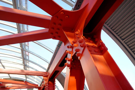 Red iron beams bolted on. Angular connection of several iron beams in one place. Pedestrian crossing with iron construction and ceiling.