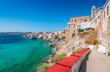 Fotomurales - Vaporia district of Ermoupoli town, Syros Island. Landscape with buildings along the coastline and stairs to the beach.
