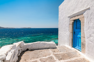 Wall Mural - Mykonos, Greece. Traditional white building with blue door at the seaside.