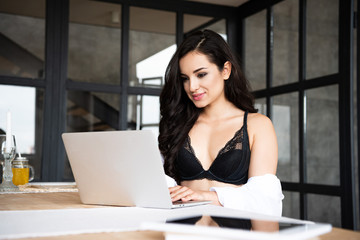 selective focus of sexy girl in black underwear and white shirt using laptop