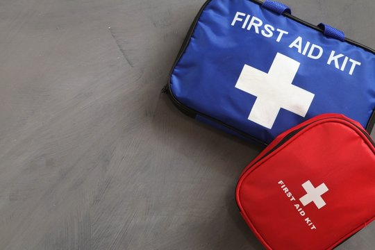 What first aid kit should you have? Blue and red first aid kits on grey background.