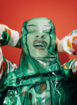 Woman squeezing face with plastic fabric