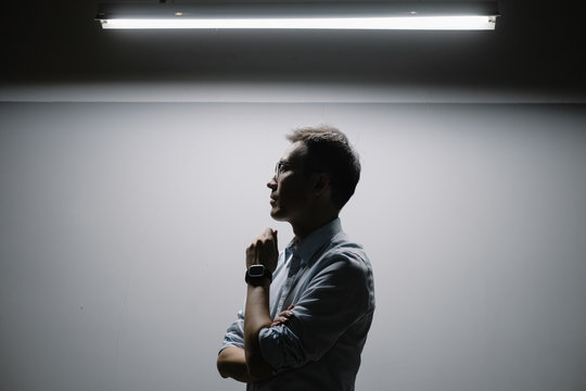 Side view of businessman standing under light