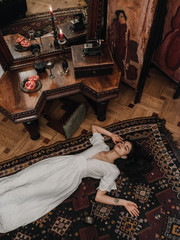 Woman lying on floor in old-fashioned room
