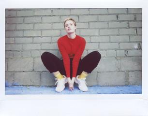 Stylish woman sitting against brick wall