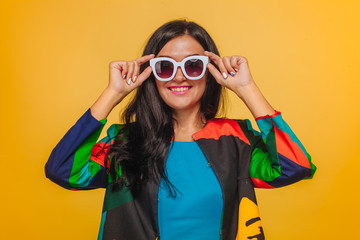 Girl on yellow background in sunglasses in bright clothes