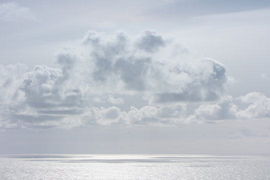 Fluffy grey clouds above a silver sea.